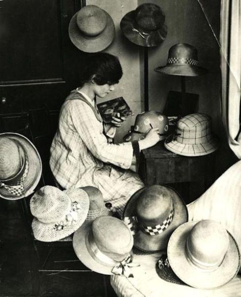 Hoedenindustrie, damesmode. Hoedenmaakster beschildert met olieverf de door haar gemaakte hoeden. Elk ontwerp is exclusief waardoor elke hoed uniek is. Kensington, Engeland, 1919.